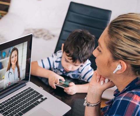 woman watching professional screencast with earbuds and child nearby
