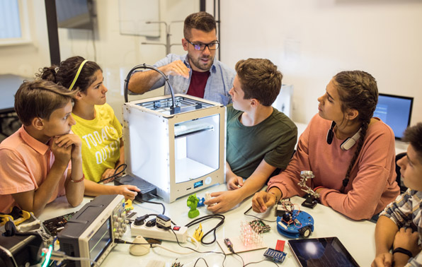 teacher working with students using a 3D printer